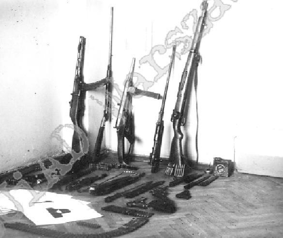"""Arsenał organizacyjny """"Warszawskich Orląt"""". Zwraca uwagę stojący przy ścianie (trzeci od lewej) pistolet maszynowy konspiracyjnej produkcji AK – """"Błyskawica"""", źródło: IPN"""